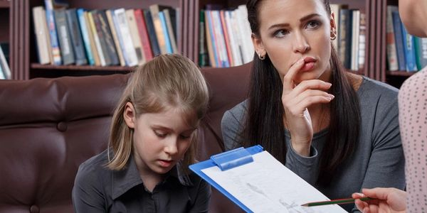 Stock photo of mother and daughter sitting on couch, listening to therapist explain chart in hand.