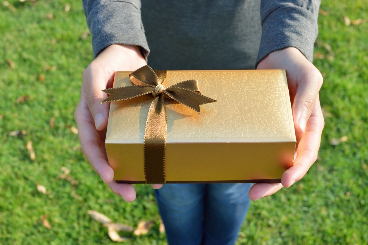 A gold box with a gold ribbon is presented as a gift.