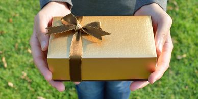 Hands holding gold gift box with gold bow.
