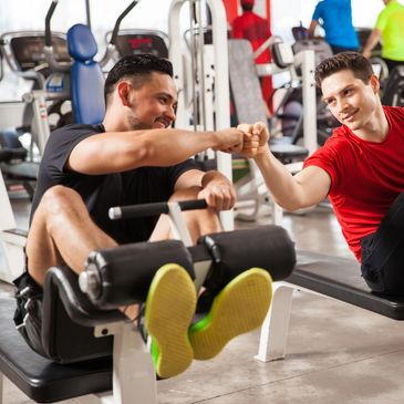 Marina Fitness Gosport Annual membership - two men on exercise machines fist bump happily
