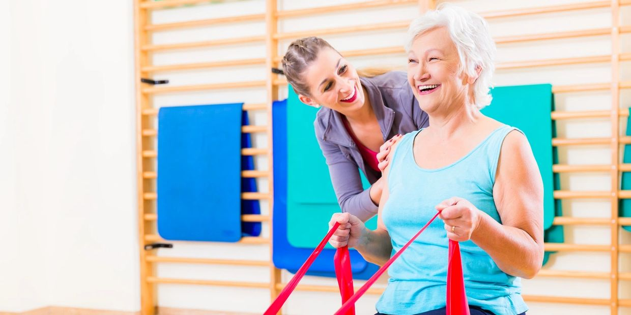 personal trainer instructing older woman