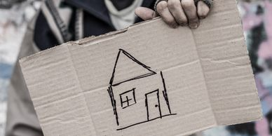 someone holding up a cardboard sign with a house drawn on it