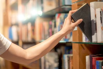 A hand reaching out and grabbing a book off the shelf in a library