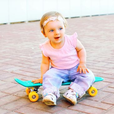 Baby wearing a headband on a skateboard