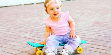 A toddler sits on a skateboard