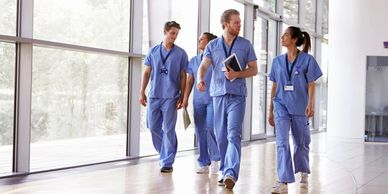 Team of doctors and nurses walking through a hospital.