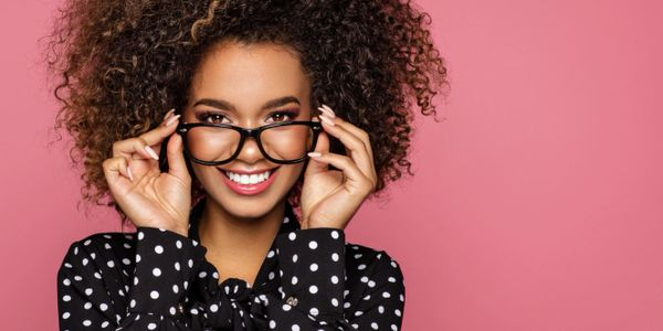 Curly hair woman holding glasses