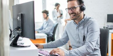 Person with a headset on working on computer and doing customer service.