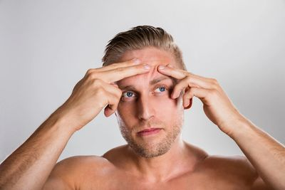Man popping a spot on his forehead
